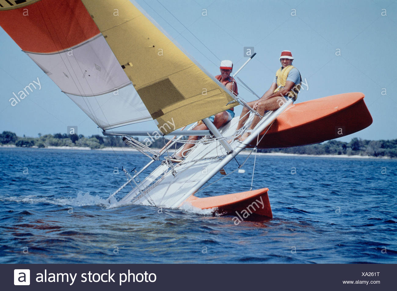 Australia. Two men sailing catamaran yacht tipping on one hull. Stock Photo