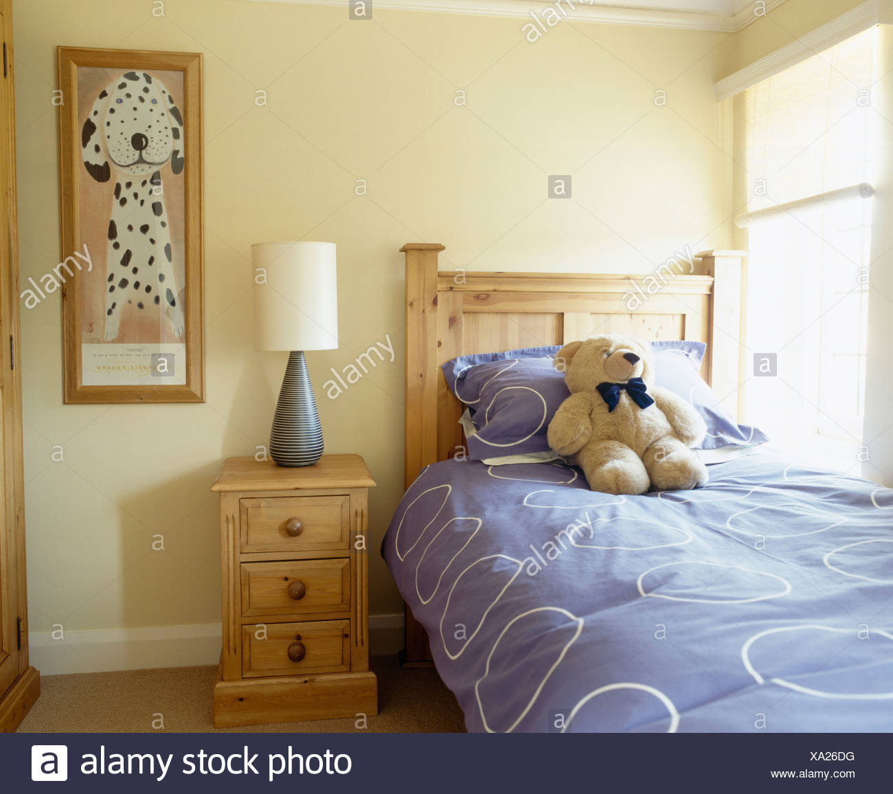 Teddy-bear and blue quilt on pine bed in child\'s cream bedroom with ...