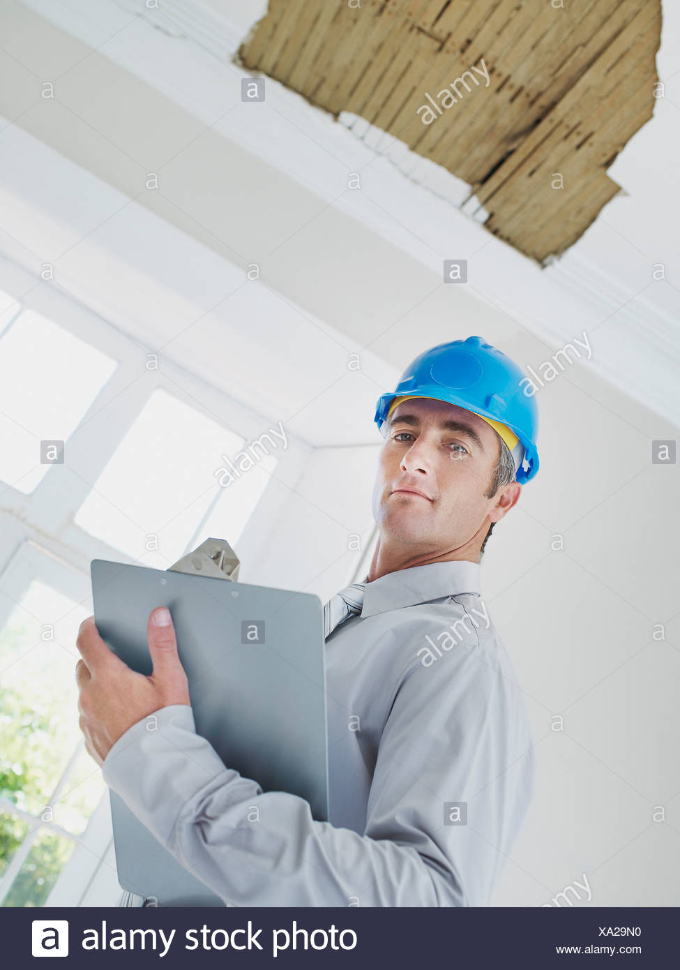 Man with clipboard and helmet in house with damaged ceiling - Stock Image