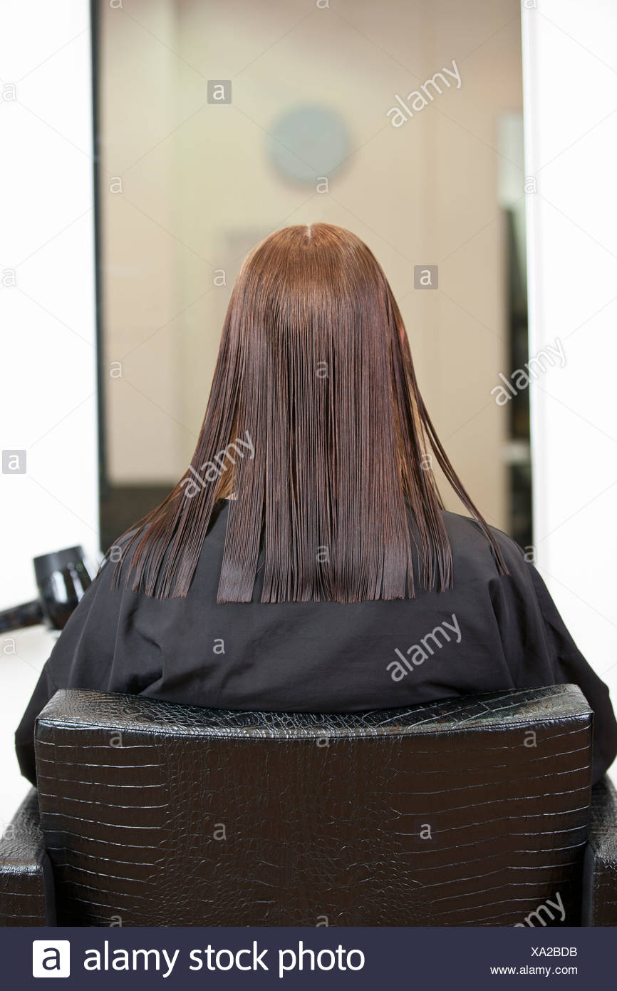 A female client looking in a mirror at a hairdressing salon, view from behind - Stock Image