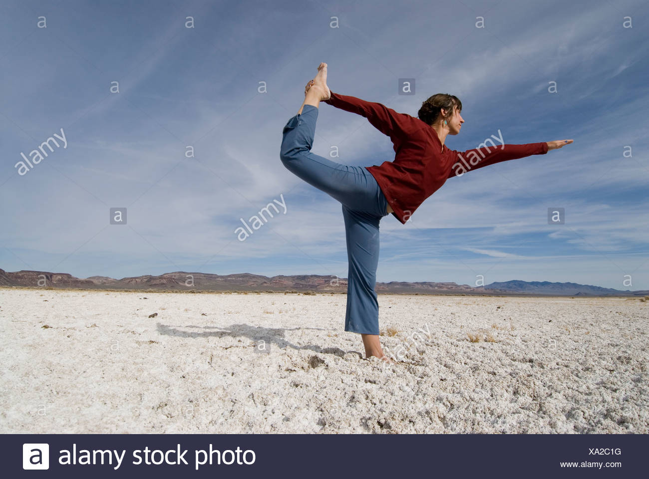 A young woman does yoga on a barren saltflat in Western Nevada. Stock Photo