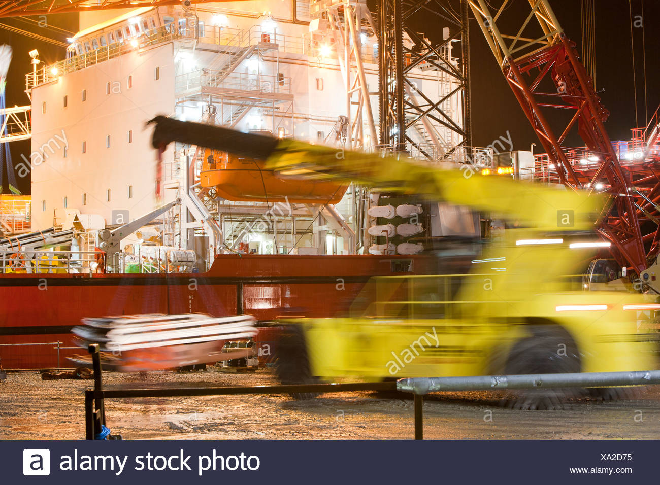 a jack up barge loading wind turbine parts on the docks at