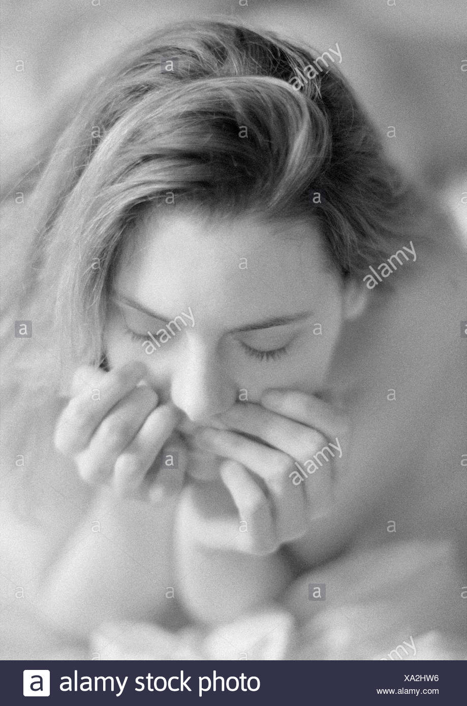 Woman lying on bed holding head in hands, portrait, close-up, black and white - Stock Image