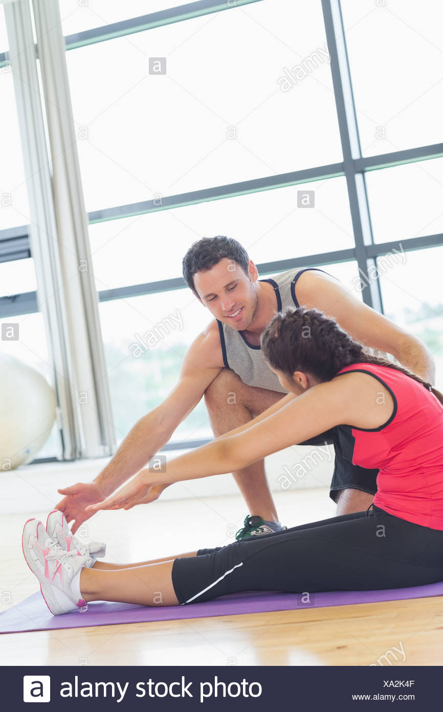 Trainer assisting woman with pilate exercises in fitness studio - Stock Image