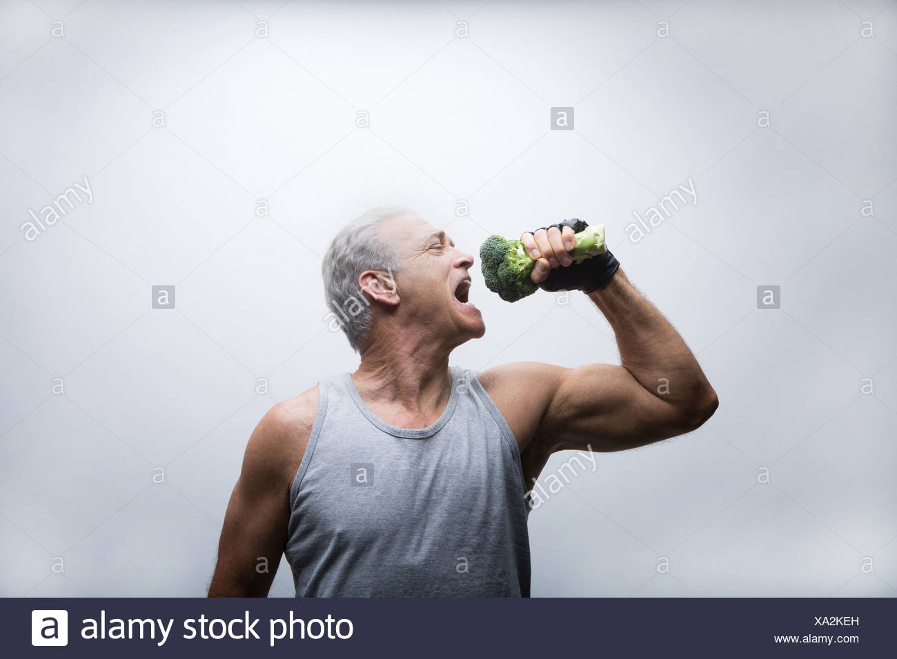 Senior man about to eat broccoli - Stock Image