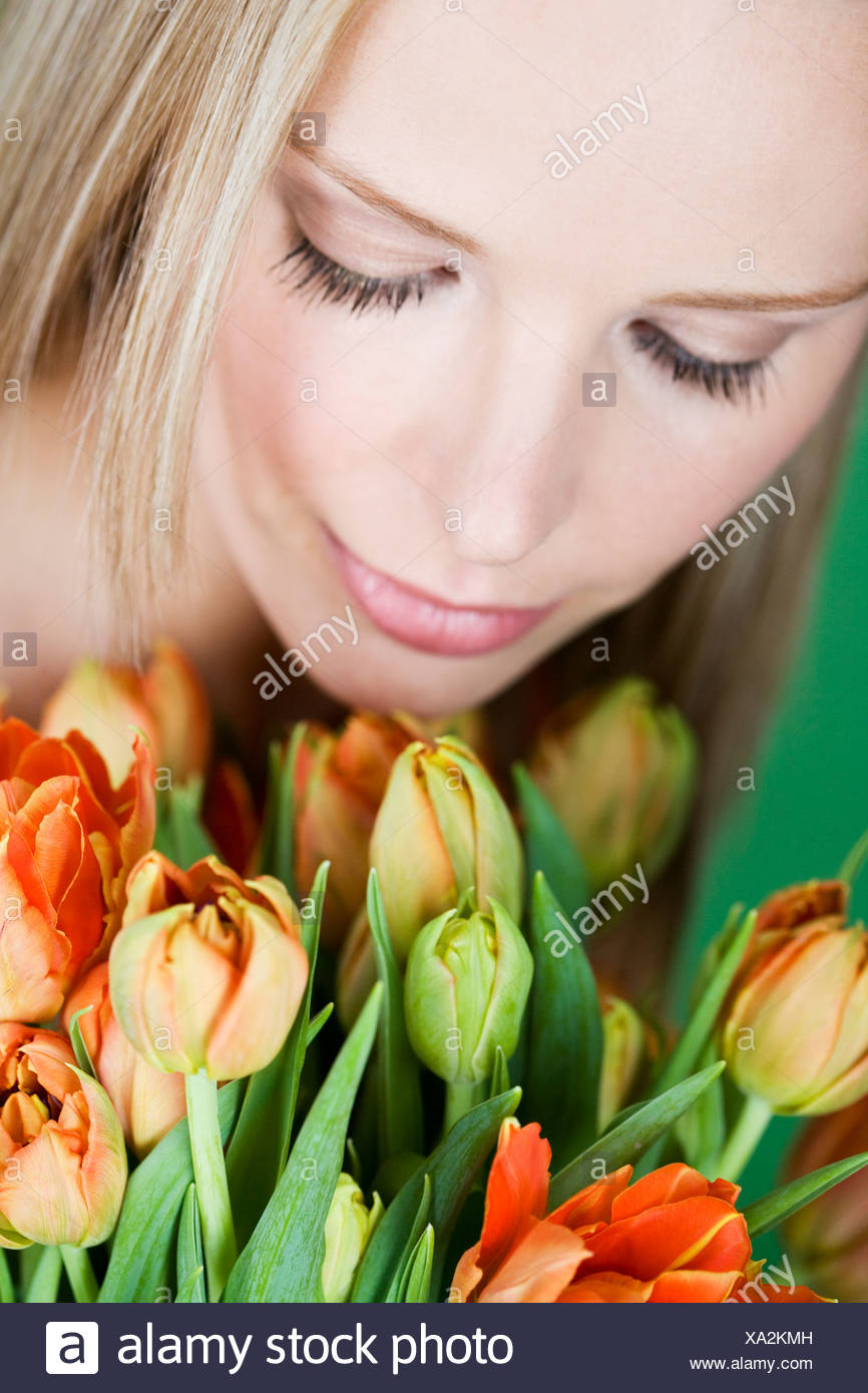 A young woman looking at a bunch of orange tulips, looking down Stock Photo