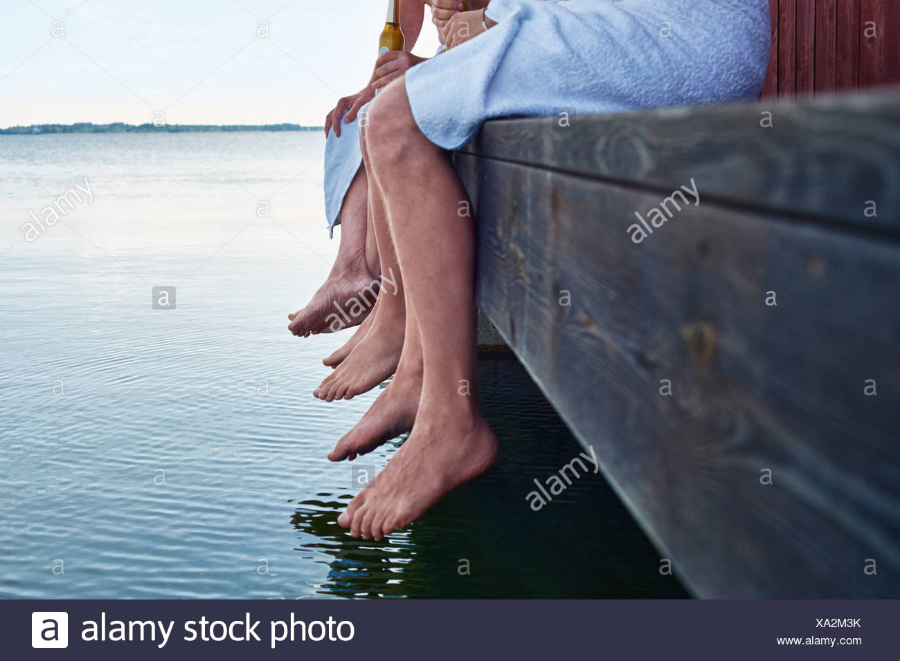 Close up of three males waist down outside sauna - Stock Image