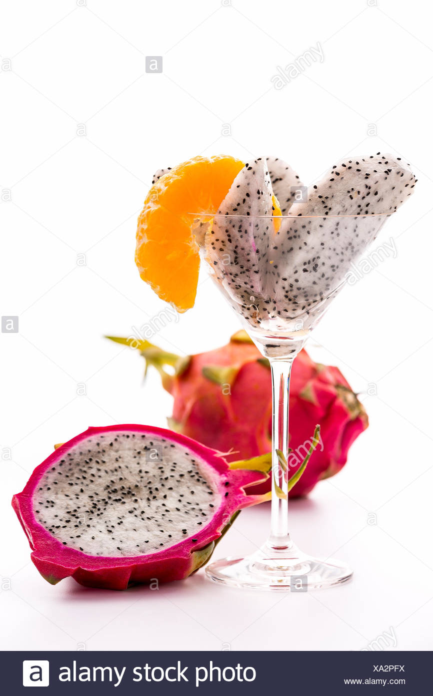 Wedges of a pitaya assorted in a glass and decorated with a mandarine slice. Next to it a halved, and behind it, an entire Fruit. - Stock Image