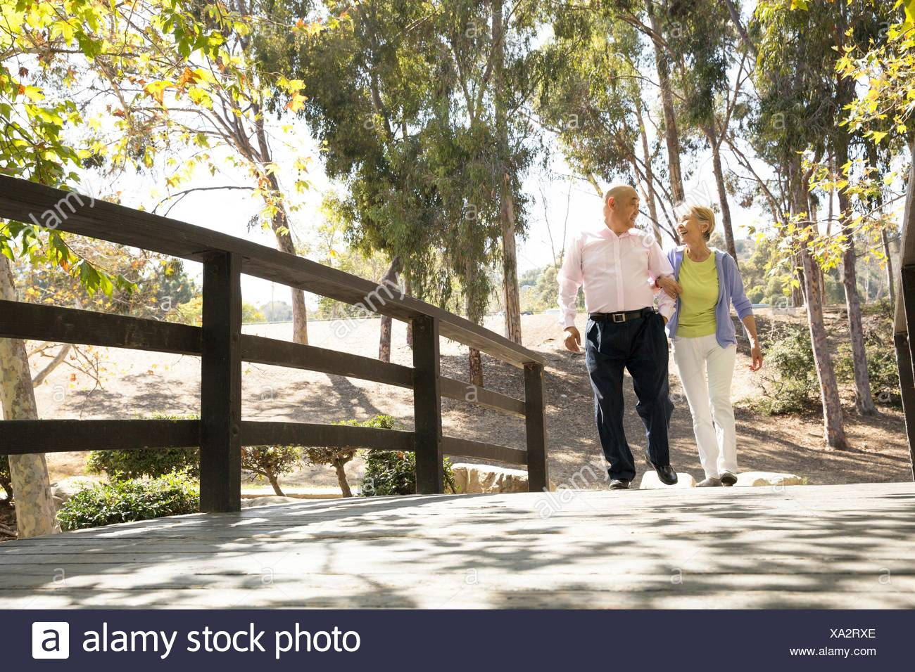 Senior couple walking arm in arm across footbridge - Stock Image