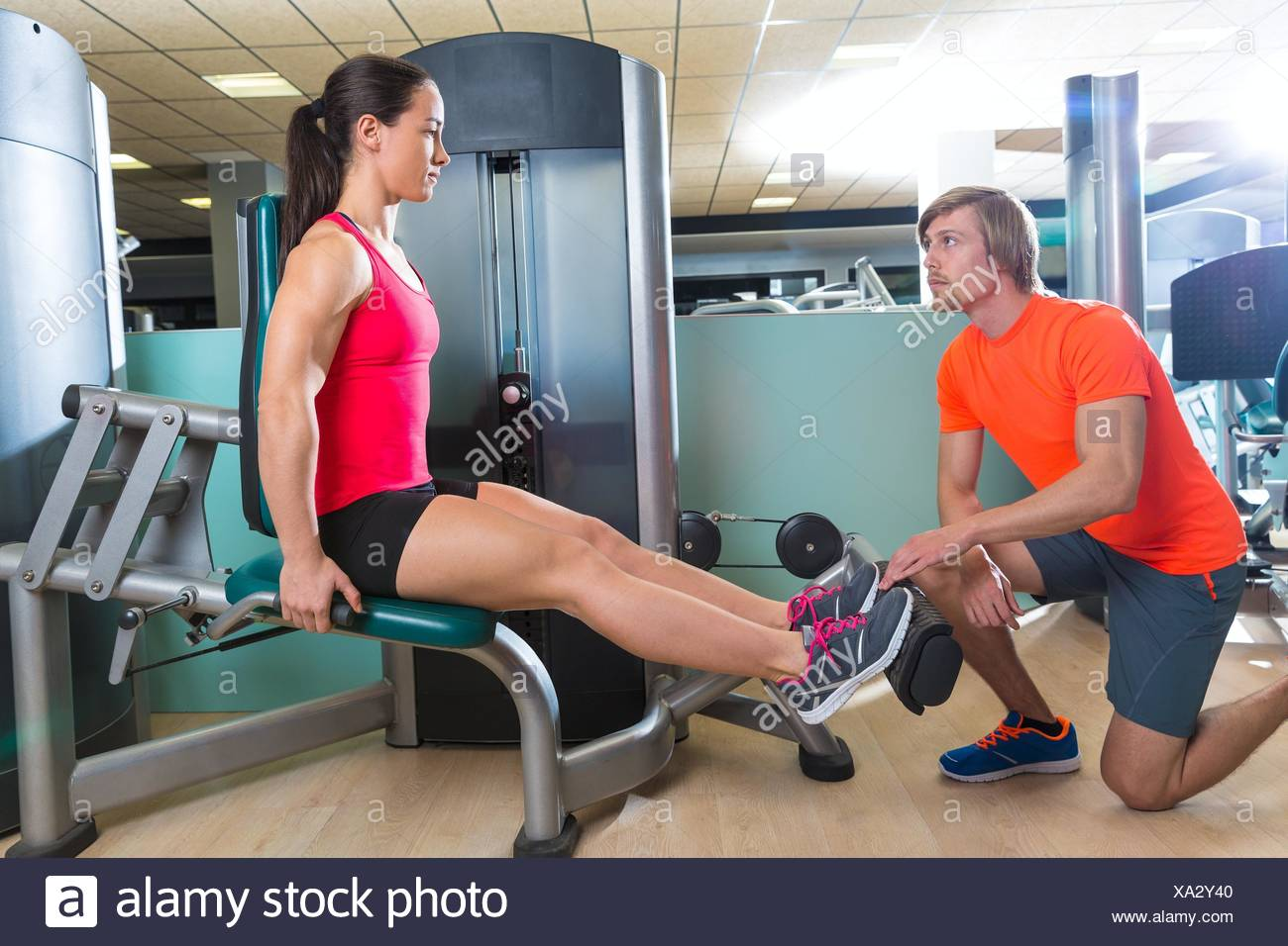Calf extension woman at gym exercise machine workout and personal trainer woman. - Stock Image