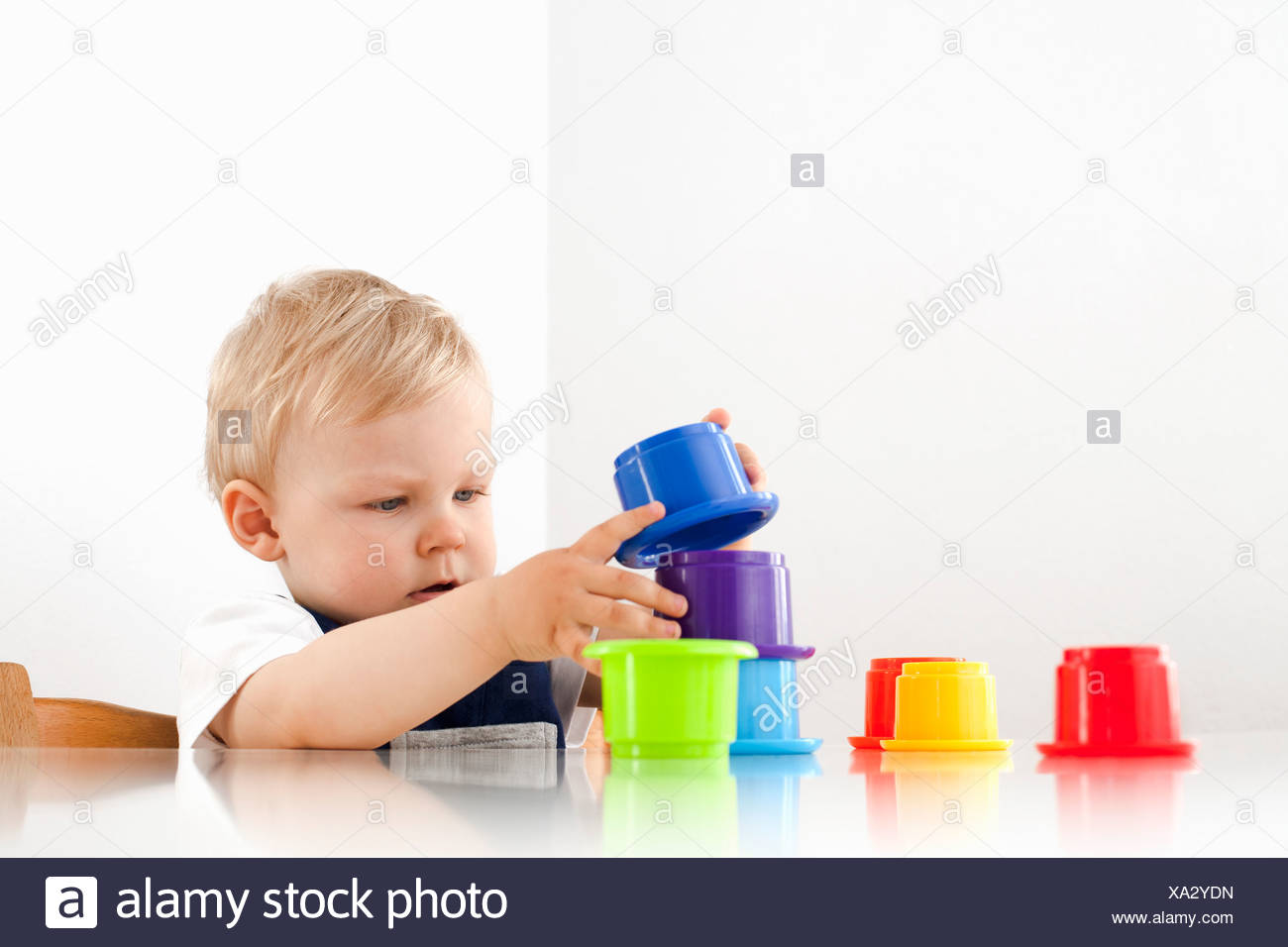 Little boy playing with stacking cups - Stock Image