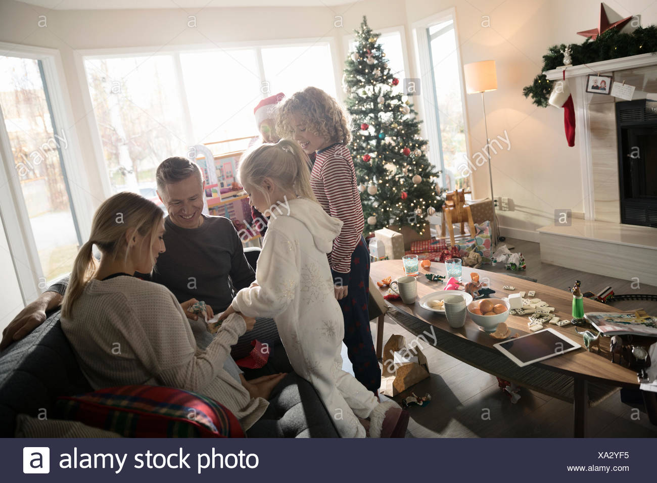 Family opening Christmas gift in living room - Stock Image
