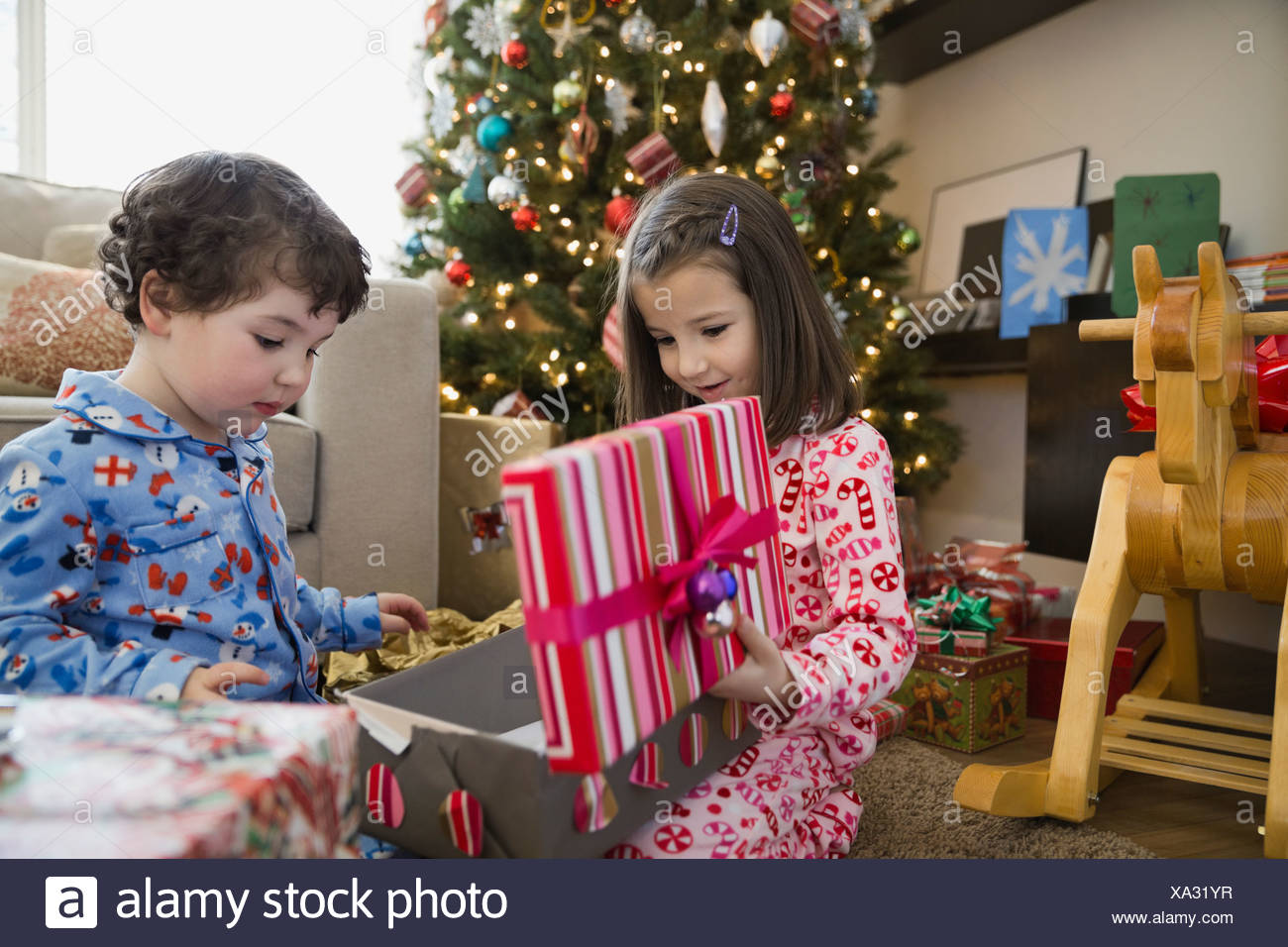 Siblings opening Christmas gift at home - Stock Image