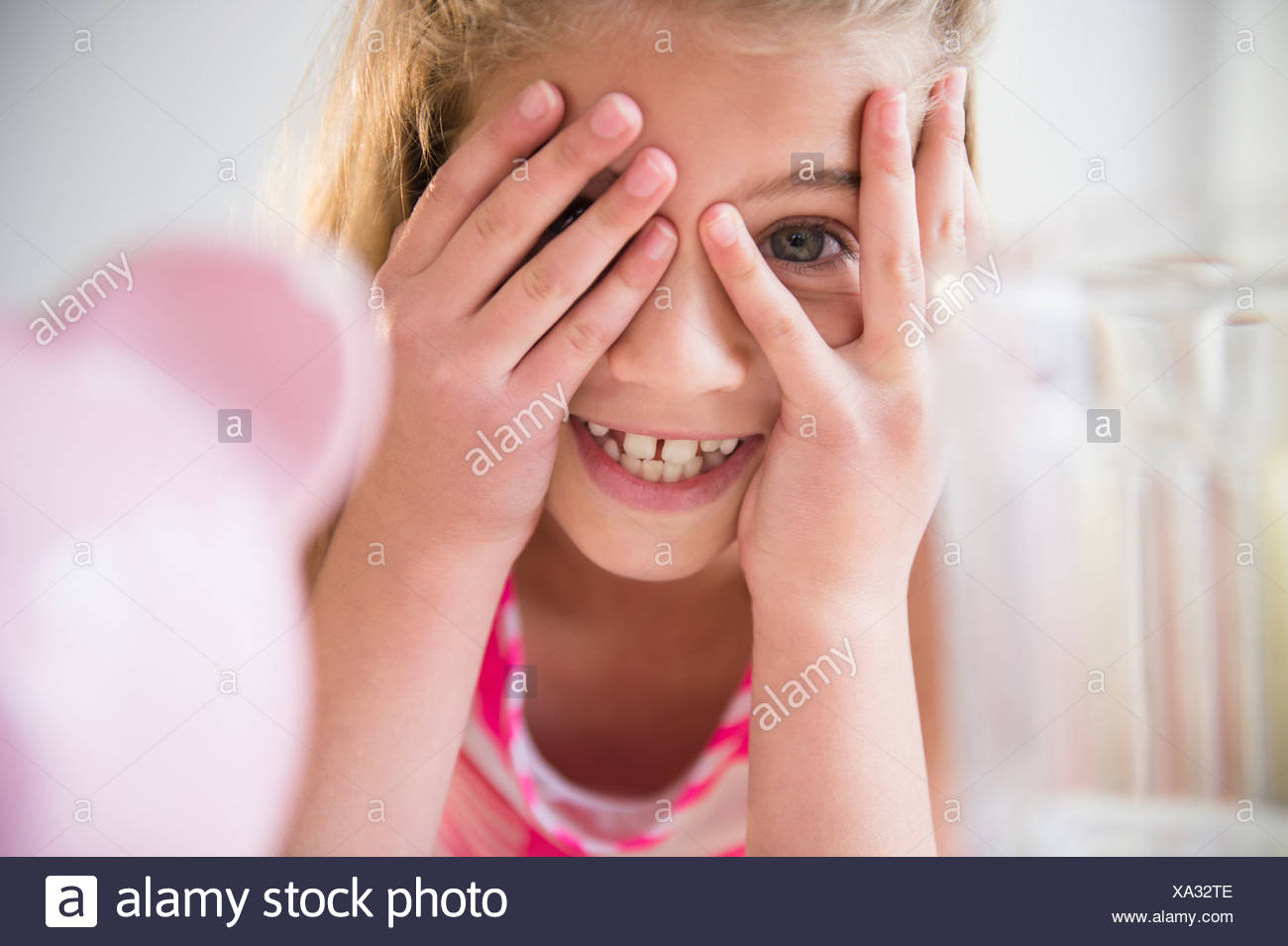 Girl (8-9) smiling and covering eyes - Stock Image
