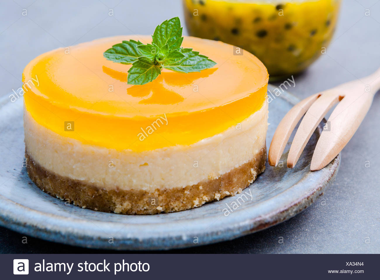 Passion fruit cheesecake with fresh mint leaves on dark backgrou - Stock Image