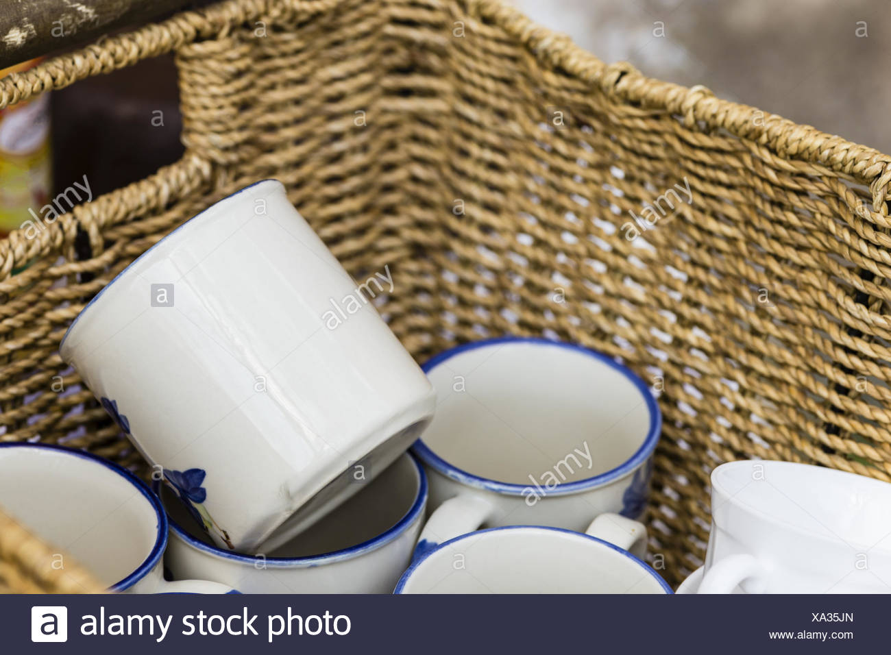 coffee mugs in a basket - Stock Image