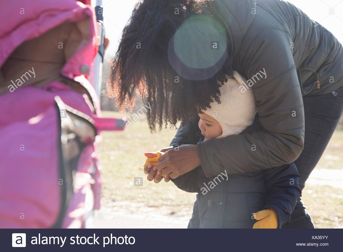Mid adult woman putting gloves on toddler daughter in park - Stock Image