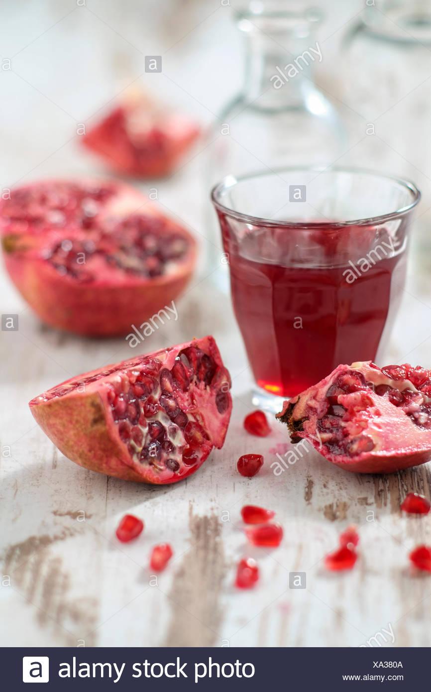 Cut open pomegranates, cores and glass near pomegranate juice - Stock Image