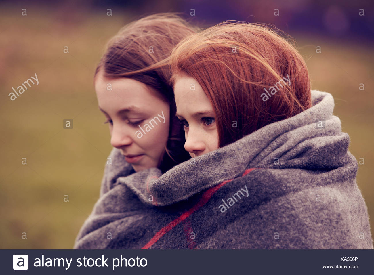 Girls wrapped in a blanket outdoors - Stock Image
