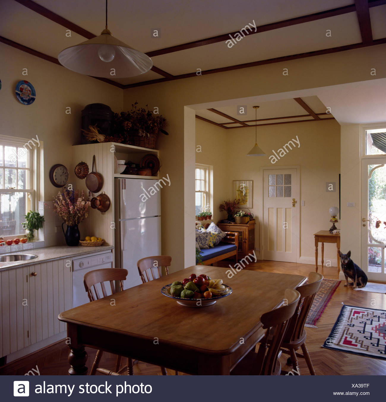 Vintage Pine Table And Chairs In An Open Plan Traditional Kitchen With A Dog Sitting
