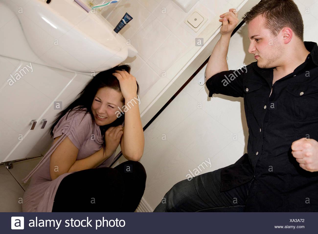 youn man beating young woman in bathroom Stock Photo