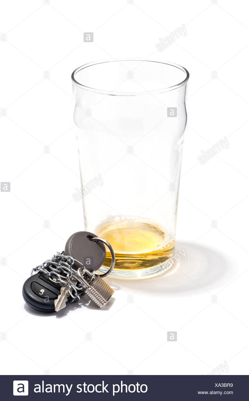 An empty pint of beer and a car key chained and padlocked - Stock Image