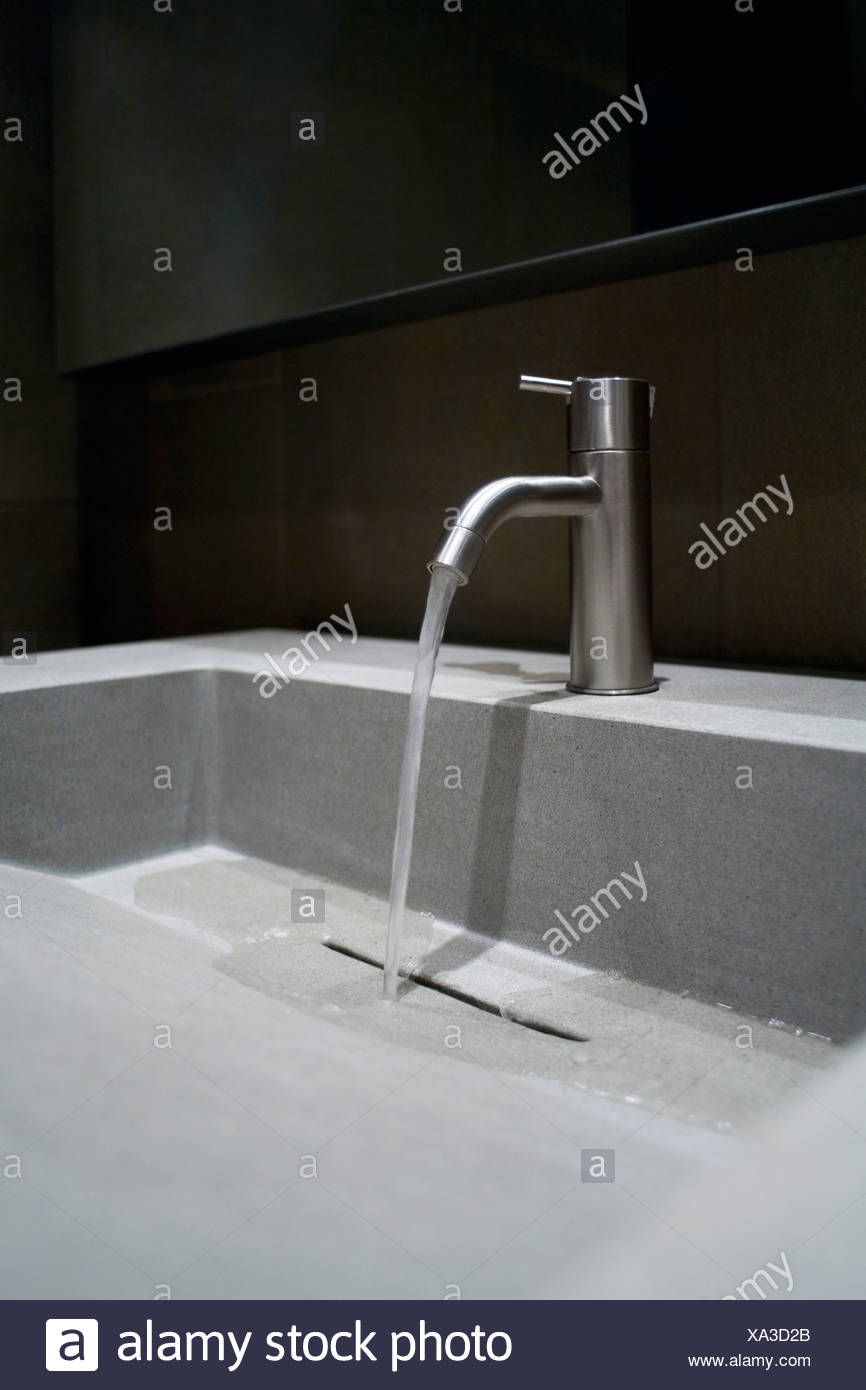 Close-up of a faucet with running water - Stock Image
