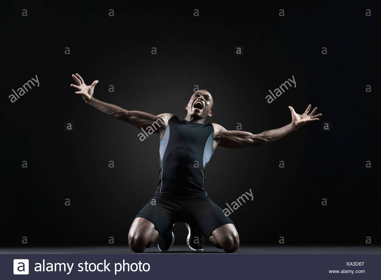 Male athlete kneeling and shouting with despair - Stock Image