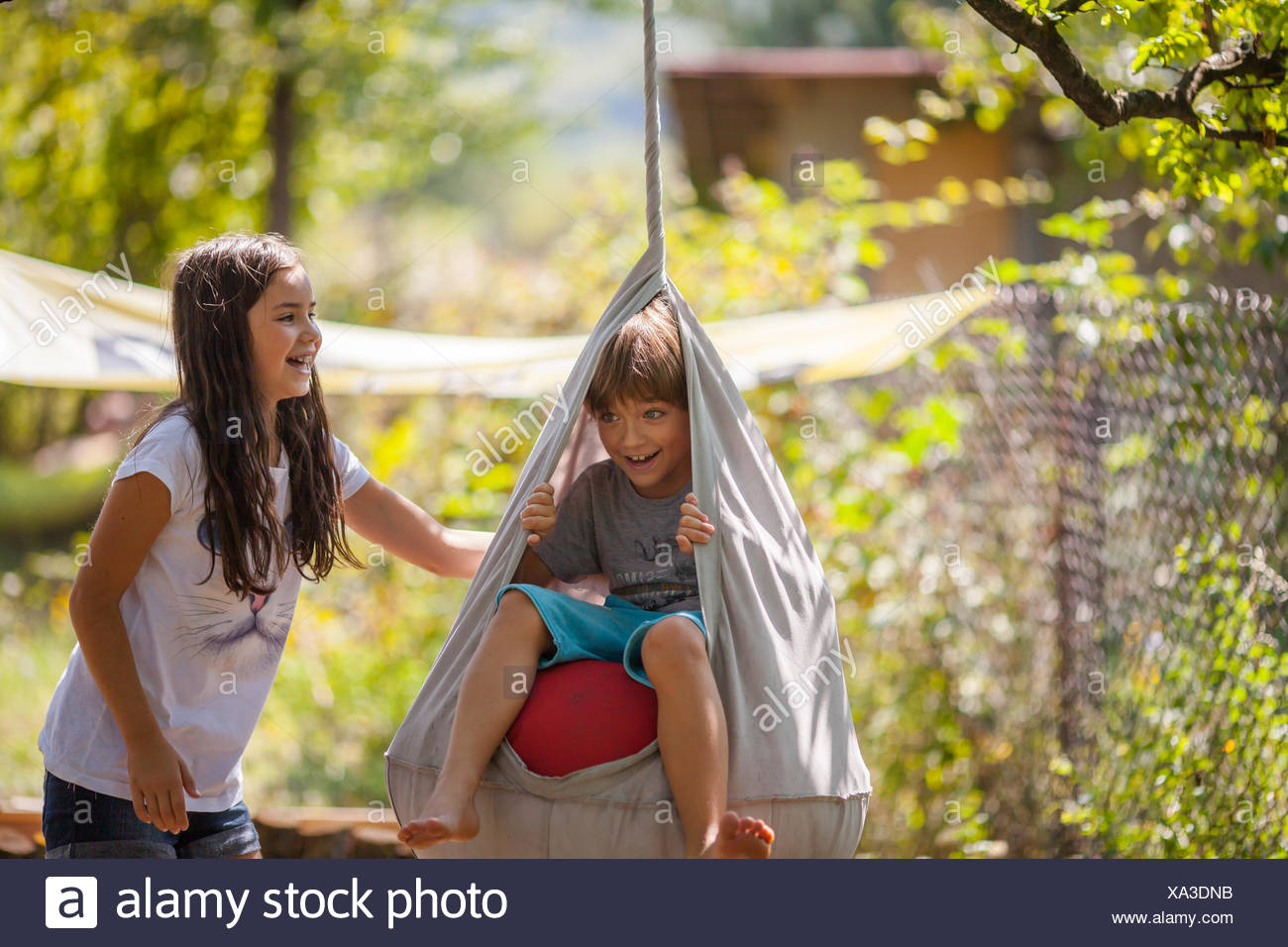 Boy and girl playing on a swing in the garden - Stock Image