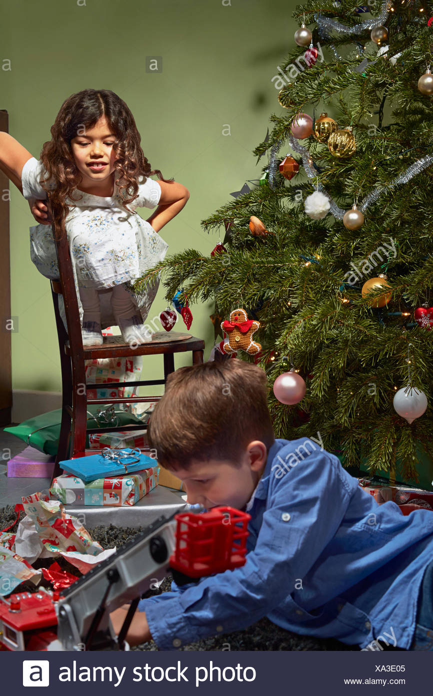 Sister watching brother in unwrapping and playing with christmas gifts - Stock Image