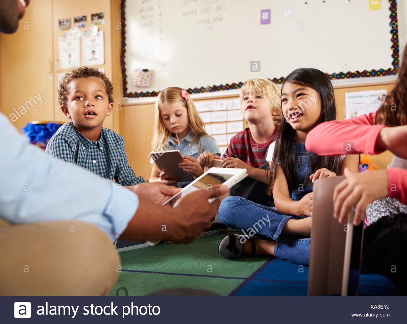 Elementary school class sitting cross legged using tablets - Stock Image