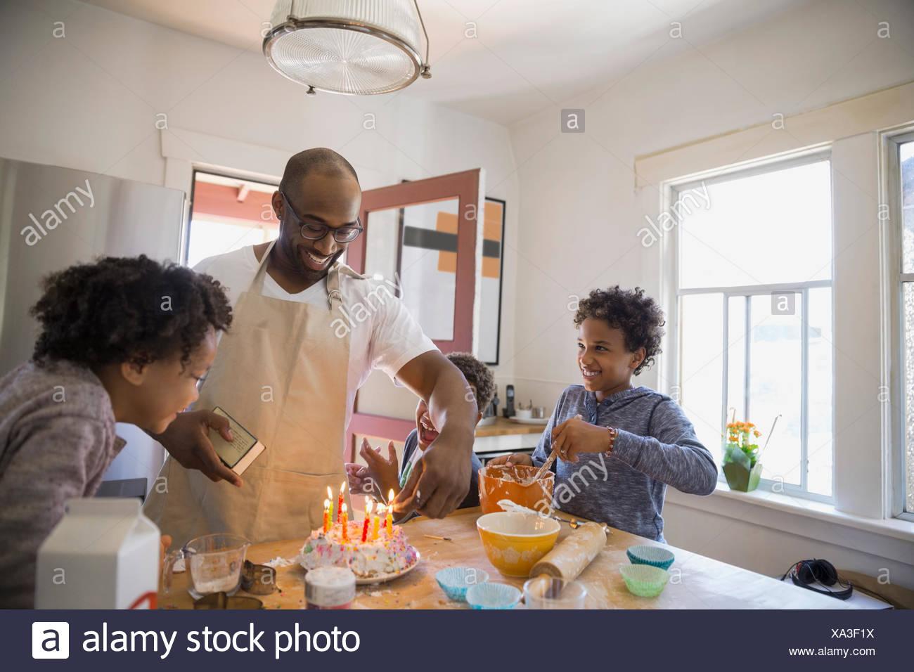 Father and children preparing birthday cake - Stock Image