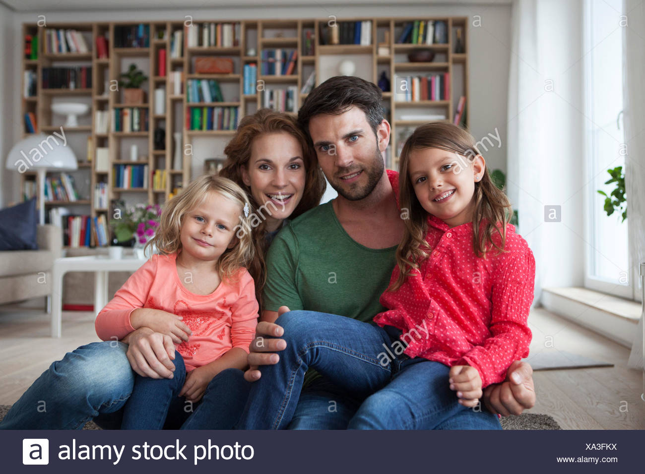 Family portrait of couple with two little girls sitting on the floor of living room - Stock Image