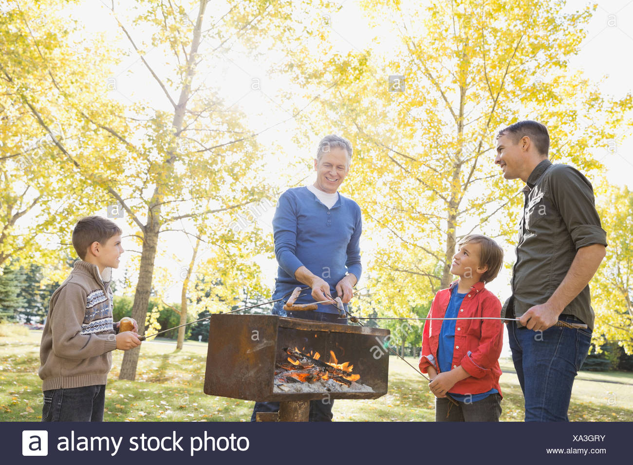 Male family members cooking hot dogs in park - Stock Image