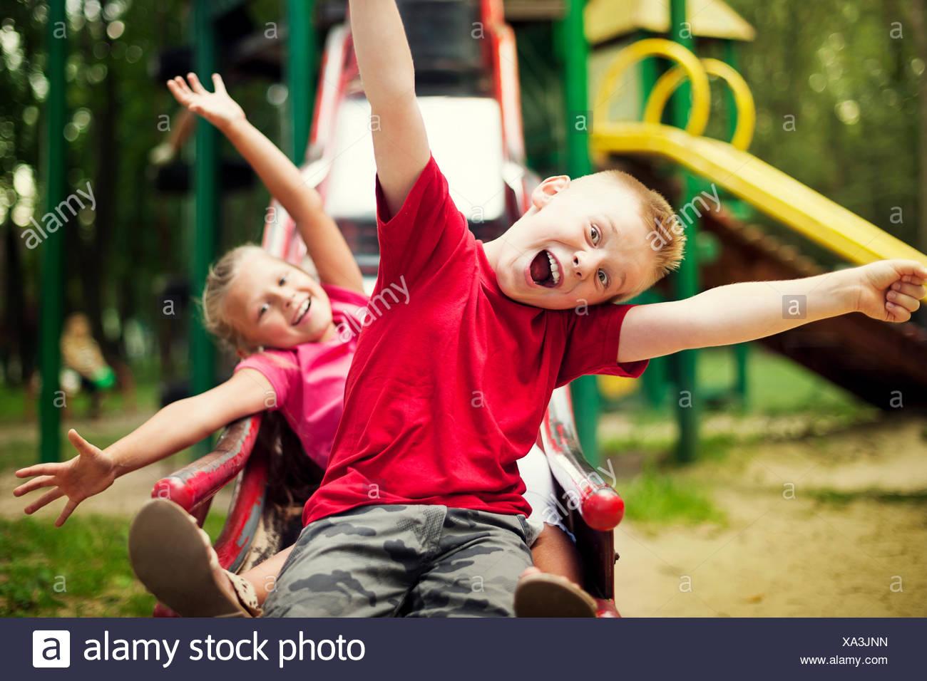 Two kids slide on playground, Debica, Poland - Stock Image