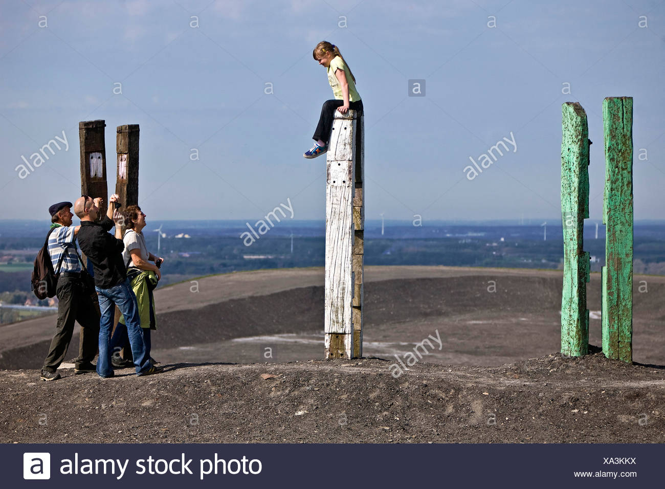 girl sitting on a totem and people taking photos at stockpile Haniel, Germany, North Rhine-Westphalia, Bottrop - Stock Image