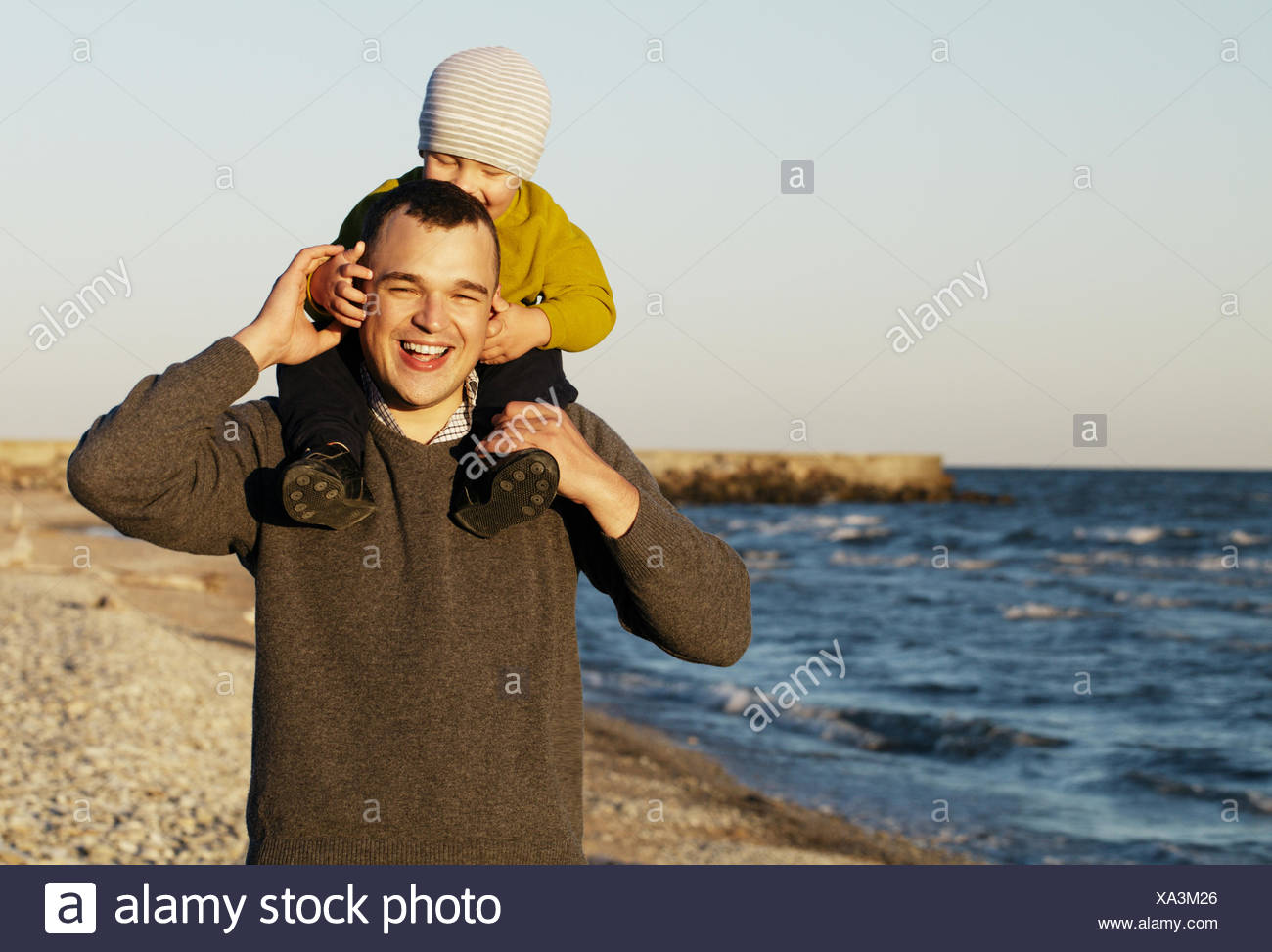 Laughing father giving his sonny a piggy back - Stock Image