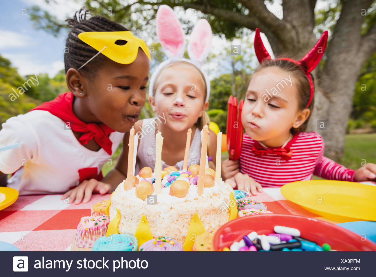 Three little girls blowing together birthday candles - Stock Image