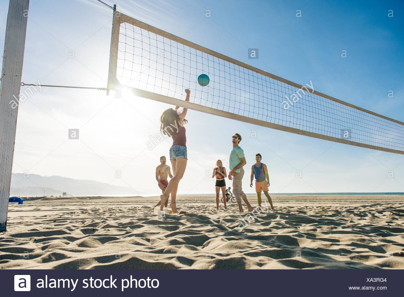 Group of friends playing volleyball on beach Stock Photo
