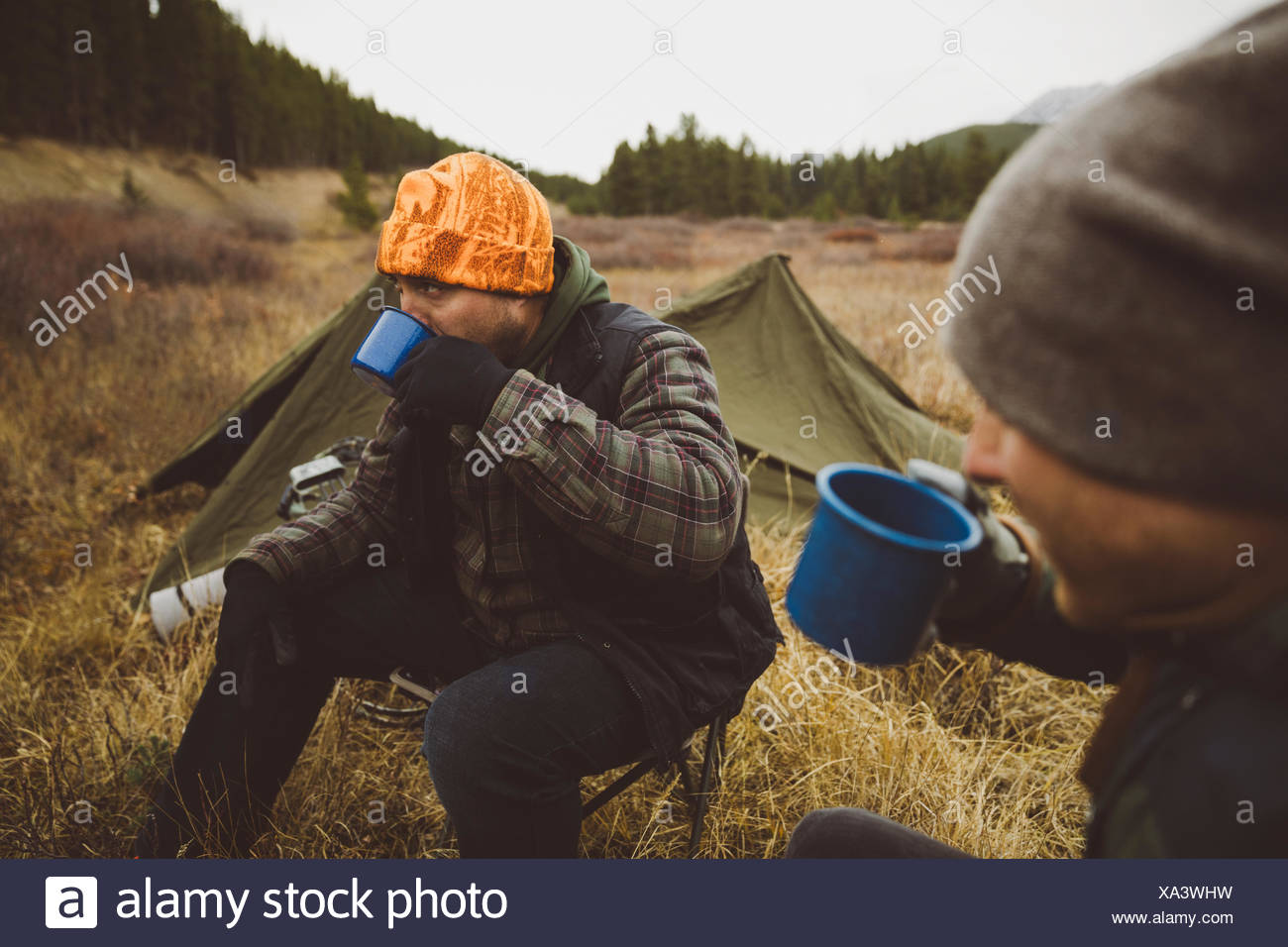 Male hunter friends drinking coffee outside tents at campsite in remote field Stock Photo