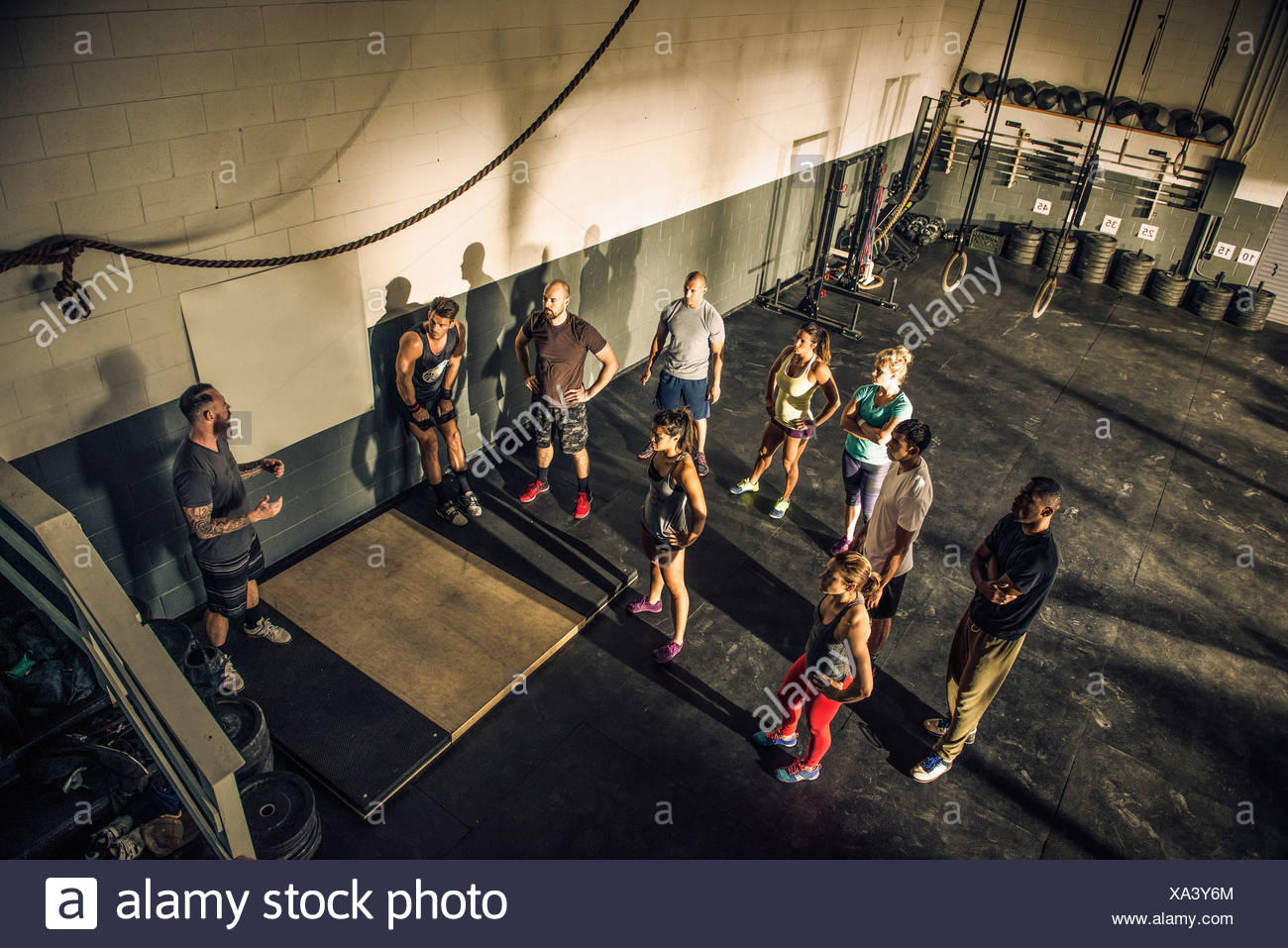 Trainer talking to fitness group in gym - Stock Image