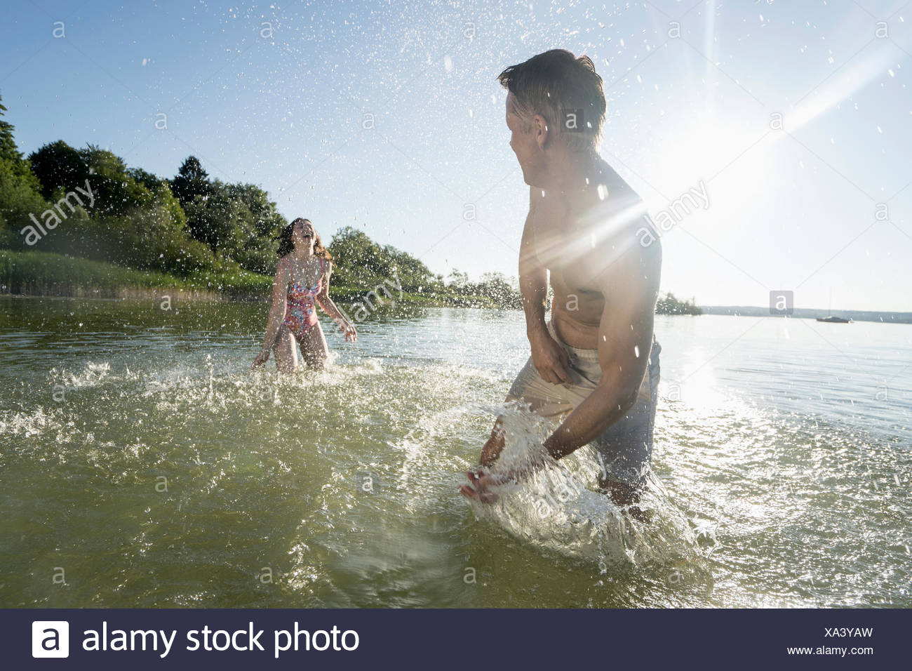 Mature couple splashing water to each other on lake, Bavaria, Germany - Stock Image