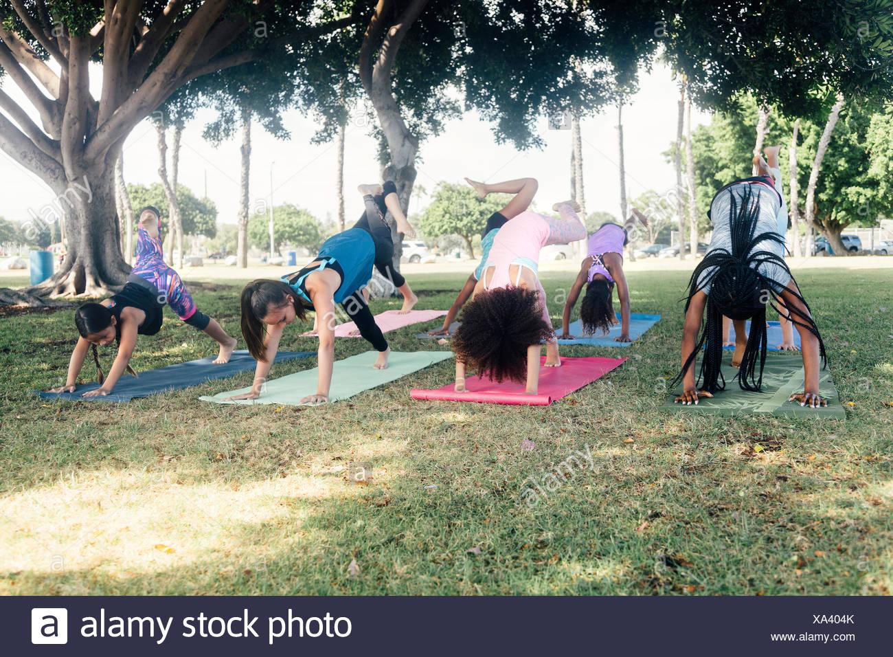 Schoolgirls practicing yoga downward facing dog on school sports field - Stock Image