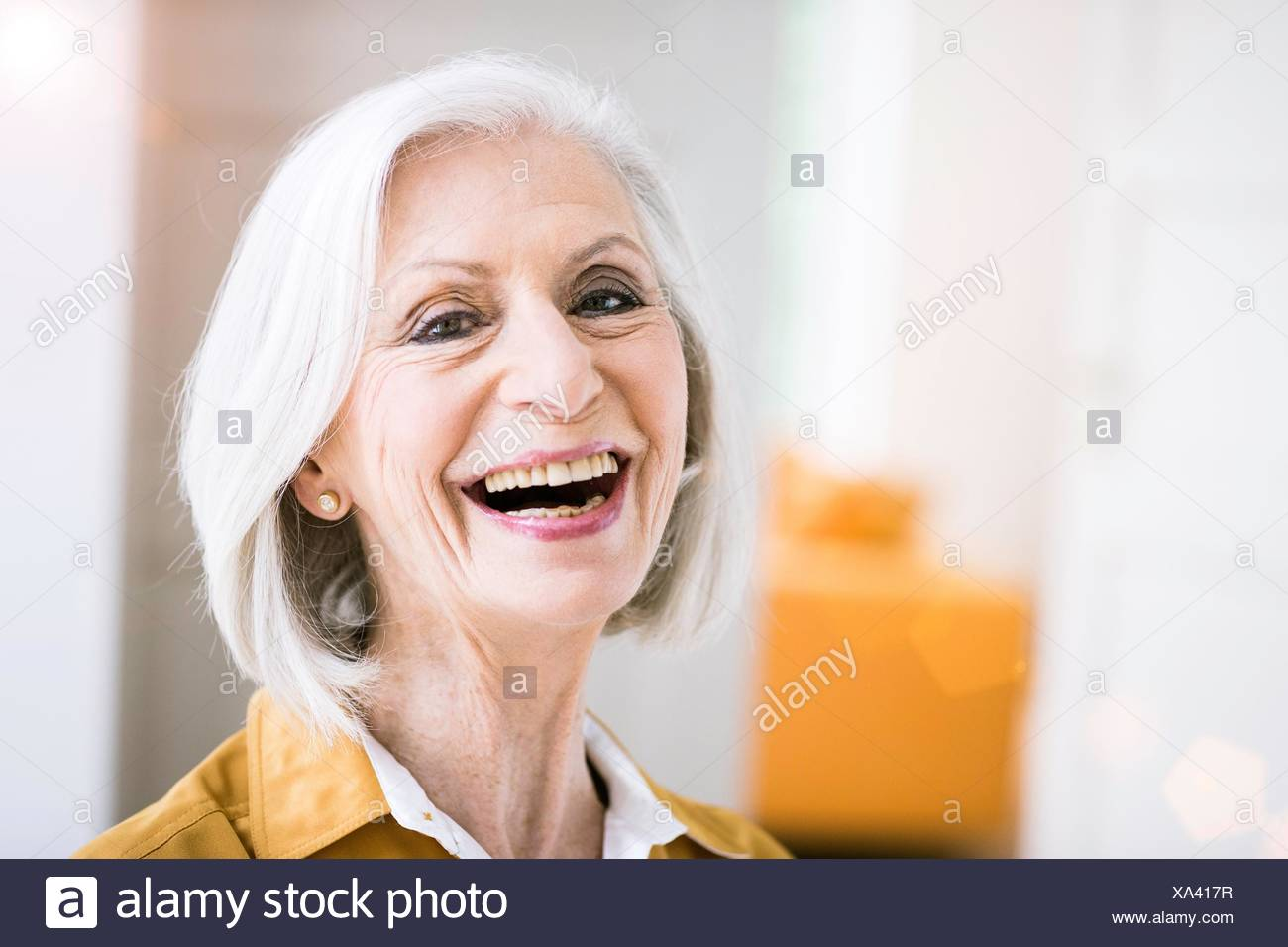 Portrait of senior woman looking at camera open mouthed smiling - Stock Image