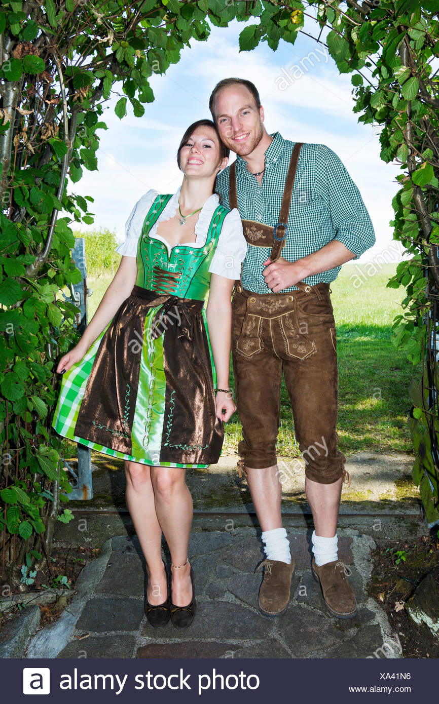 bavarian couple standing underneath a tree - Stock Image