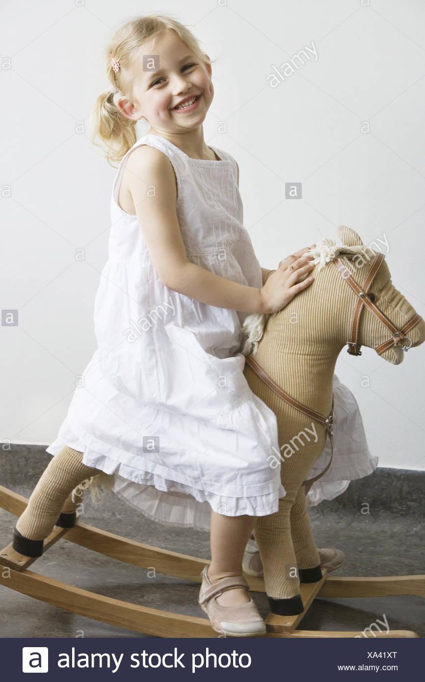 Preschool girl sitting on rocking horse - Stock Image