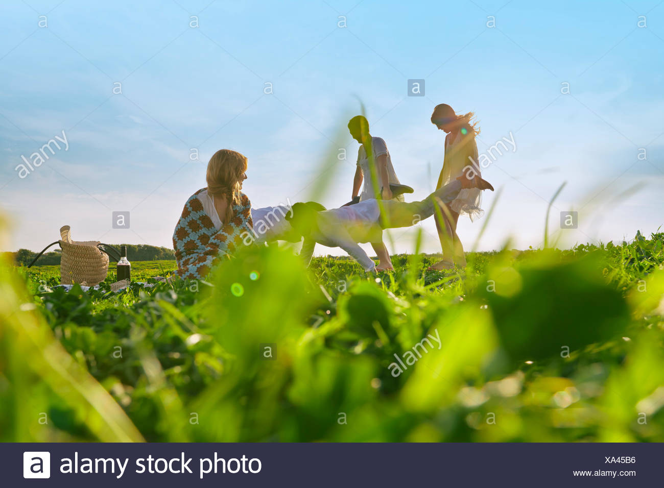 Group of young adult friends having pretend wheelbarrow race in field - Stock Image