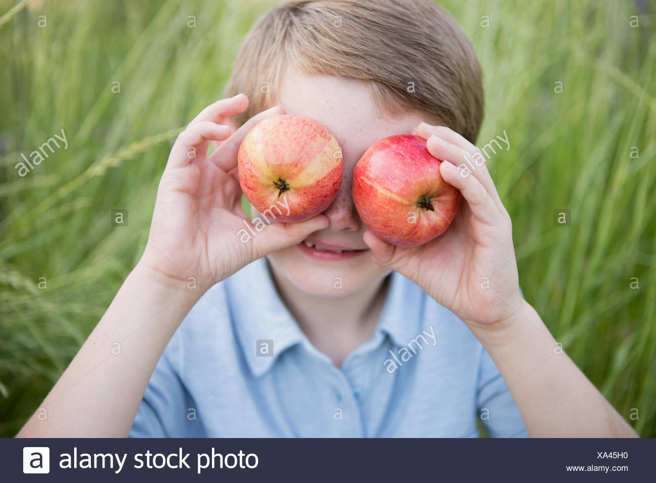 A boy holding two red skinned apples over his eyes. - Stock Image