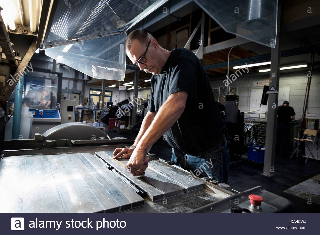 Worker servicing print machine in printing workshop - Stock Image