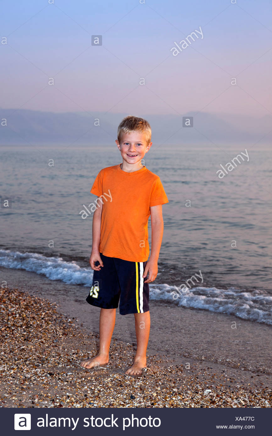Boy, 7, in the evening on a pebble beach, Corfu, Ionian Islands, Greece, Southern Europe, Europe - Stock Image